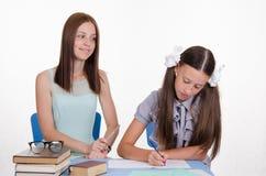 De leraar kijkt positief op het studentenmeisje Stock Foto's