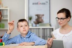 De leraar met notitieboekje neemt jongen waar Royalty-vrije Stock Fotografie