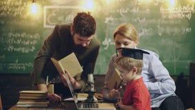 De leraar moedigt de jongen aan om te bestuderen Het boek van leraarsaanbiedingen aan de jongen op school De jongen negeert lerar stock videobeelden