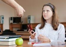 De leraar neemt mobiele telefoon bij les in beslag Stock Foto