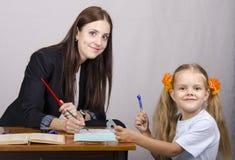 De leraar onderwijst lessen met een studentenzitting bij de lijst Stock Foto's