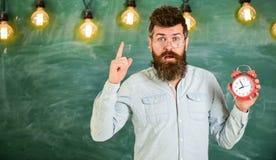 De leraar in oogglazen houdt wekker Gebaarde hipster houdt klok, die met wijsvinger, exemplaarruimte waarschuwen discipline stock foto
