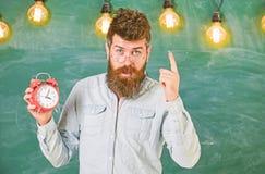 De leraar in oogglazen houdt wekker Gebaarde hipster houdt klok, die met wijsvinger, exemplaarruimte waarschuwen discipline stock afbeelding