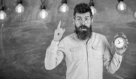 De leraar in oogglazen houdt wekker Gebaarde hipster houdt klok, die met wijsvinger, exemplaarruimte waarschuwen discipline stock fotografie