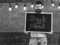 De leraar op verdacht gezicht houdt bord met titel terug naar school De mens met baard heet welkom studenten, bord royalty-vrije stock foto's