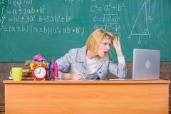De leraar schokte gezicht houdt werkend na klassen De leraarsvrouw zit het bordachtergrond van het lijstklaslokaal Het werk ver stock foto's