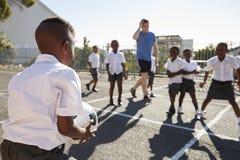 De leraar speelt voetbal met jonge jonge geitjes in schoolspeelplaats Stock Afbeelding