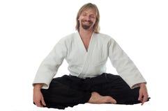 De leraar van de kalmering van aikido zit en glimlacht Royalty-vrije Stock Foto's