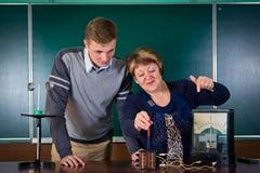 De leraar van fysica verklaart aan de leerling interactie van ma stock afbeelding
