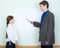 De leraar verklaart iets aan het schoolmeisje Stock Fotografie
