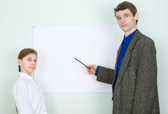 De leraar verklaart iets aan het schoolmeisje Stock Afbeeldingen