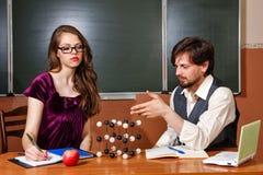 De leraar verklaart structuur van kristalrooster van student Stock Afbeelding