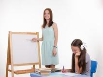De leraar verklaart taak bij bord Royalty-vrije Stock Afbeeldingen
