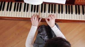 De les van de muziek Het meisje leert om de piano te spelen Mening vanaf de bovenkant stock footage