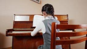 De les van de muziek Het spelen van het meisje piano Schuifmening van het spelen van rug van het kind stock footage