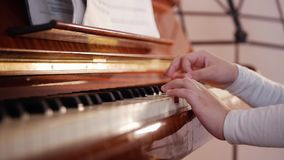 De les van de muziek Het spelen van het meisje piano Sluit omhoog op pianosleutels, kindhanden en vingers Schuifmening van het sp stock footage