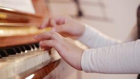De les van de muziek Het spelen van het meisje piano Sluit omhoog op pianosleutels, kindhanden Schuifmening van het spelen stock footage