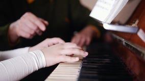 De les van de muziek Meisje het spelen de piano, oudere leraar zit dichtbij en speelt met meisje Mening van rechterkant stock video