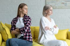 De lesbische wijfjes koppelen in vrijetijdskleding rijtjes zitten aan crosed handen op gele bank na ruzie stock afbeeldingen