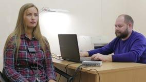 De leugendetectortest, een vrouw beantwoordt de vragen van de deskundige stock video