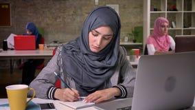 De leuke Arabische vrouw in hijab schrijft nota's neer en controleert haar laptop, die vibes, collega's, diverse modern erachter  stock videobeelden