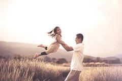 De leuke Aziatische glimlach en de pret van het kindmeisje terwijl vader die haar jong geitje houden Stock Fotografie