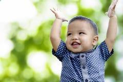 De leuke Aziatische jongen heft handen en glimlach op stock foto's