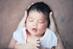 De leuke Aziatische pasgeboren slaap van het babymeisje in moederhand Royalty-vrije Stock Afbeelding