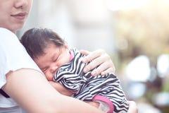 De leuke Aziatische pasgeboren slaap van het babymeisje op moeder` s borst Stock Fotografie
