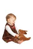De leuke baby bekijkt veel liefs gevuld stuk speelgoed Stock Afbeeldingen