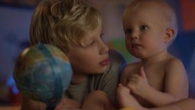 De leuke baby die enkel bij slecht zitten en met bol en zijn broer spelen maakt bedrijf stock video
