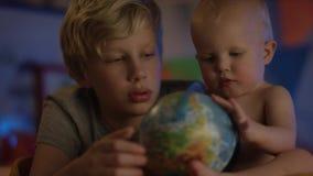 De leuke baby die enkel bij slecht zitten en met bol en zijn broer spelen maakt bedrijf tot dichte omhooggaand stock video
