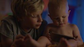 De leuke baby die enkel bij slechte en het letten op beeldverhalen met telefoon en zijn broer zitten maakt grappig bedrijf stock videobeelden