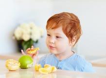 De leuke baby die van de roodharigepeuter oranje plakken en appelen proeven bij de keuken Royalty-vrije Stock Foto