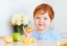 De leuke baby die van de roodharigepeuter oranje plakken en appelen proeven bij de keuken Stock Afbeeldingen