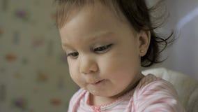 De leuke baby gil zitting in het voeden zit en het eten van gezond voedsel op keuken voor stock footage