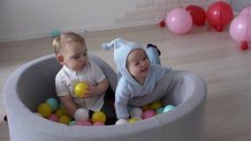 De leuke baby let op hoe een andere jong geitjepret in een pool van multicolored ballen valt stock videobeelden
