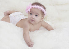 De leuke baby met roze boog ligt in de woonkamer Weinig ANG Stock Foto's