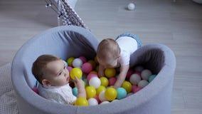 De leuke baby wil in een pool van plastic ballen aan zijn vriend krijgen, maar hij ontbreekt stock footage