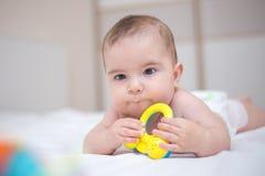 De leuke babyjongen speelt met rammelaar royalty-vrije stock afbeelding