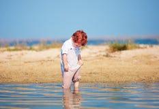 De leuke de babyjongen van de roodharigepeuter doorweekt kleren in ondiep water bij ochtendmeer stock afbeelding