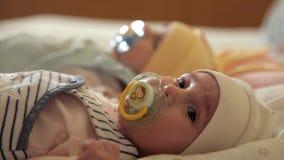 De leuke babystweelingen zijn op stadium en zuigen op een fopspeen stock footage