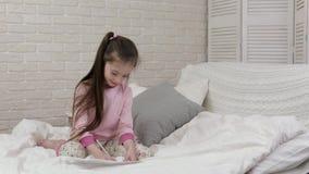 De leuke beelden van de meisjetekening terwijl het liggen op bed stock video