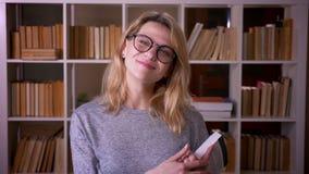 De leuke blondeleraar die op middelbare leeftijd een boek houden glimlacht in camera bevestigend haar glazen bij de bibliotheek stock videobeelden