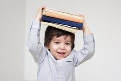 De leuke boeken van de jongensholding op zijn hoofd royalty-vrije stock fotografie