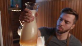 De leuke brouwer controleert vers gebrouwen bier-blikken bij zijn kleur, dichtheid, transparantie op de achtergrond van de brouwe stock videobeelden