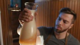 De leuke brouwer controleert vers gebrouwen bier-blikken bij zijn kleur, dichtheid, transparantie op de achtergrond van de brouwe stock footage