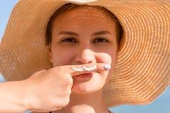 De leuke die vrouw stelt met snor met zonroom op haar vinger onder haar neus bij de overzeese achtergrond wordt getrokken royalty-vrije stock fotografie