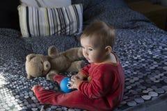 De leuke eerlijke zitting van het babymeisje bij bed het spelen met grote blauwe rubbereend en uitstekende teddybeer stock fotografie