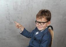 De leuke Europese jongen in een jasje met een vlinder richt zijn vinger op de muur royalty-vrije stock afbeeldingen